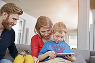 Family of four with digital tablet on couch - RHF001457