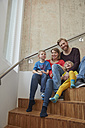 Portrait of smiling family sitting on stairs - RHF001463