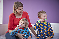 Mother with two children brushing teeth - RHF001469