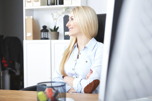 Portrait of smiling blond woman sitting at desk in her home office - SEGF000485