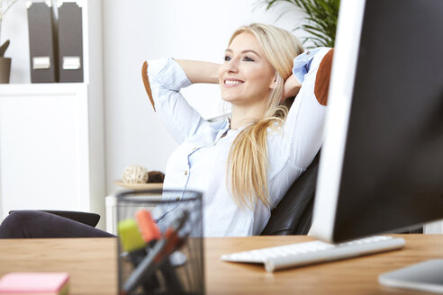 Portrait of smiling blond woman  relaxing with hands behind her head at desk in the office - SEGF000488