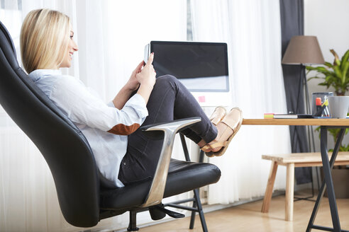 Smiling blond woman sitting at desk with feet up looking at her smartphone - SEGF000491