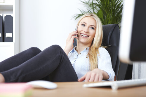 Portrait of smiling blond woman sitting at her desk with feet up telephoning with smartphone - SEGF000494