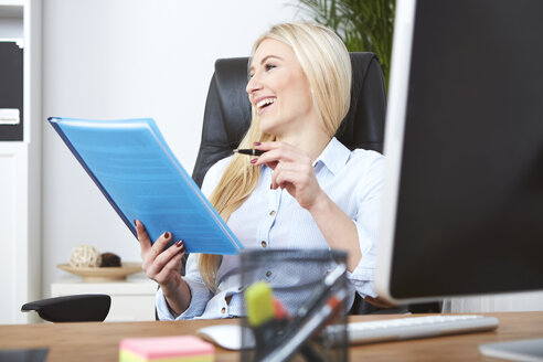 Smiling blond woman sitting at desk holding documents - SEGF000500
