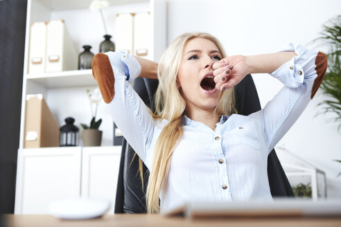 Portrait of blond woman yawning at her desk - SEGF000503