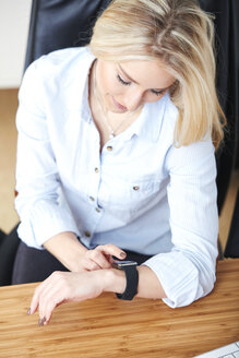 Blond woman looking at her smartwatch - SEGF000506
