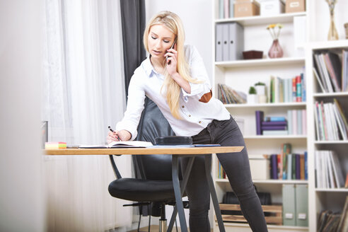 Woman writing down something at  desk in her home office while telephoning - SEGF000509