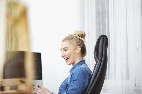 Laughing blond woman sitting at desk using digital tablet - SEGF000515