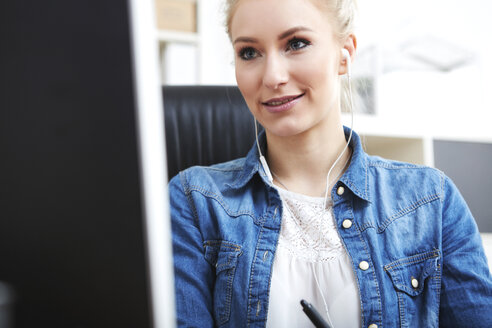 Smiling blond woman with earphones sitting at desk looking at computer - SEGF000521