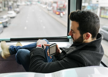 UK, London, young man in a double-decker bus using his smartwatch - MGOF001696