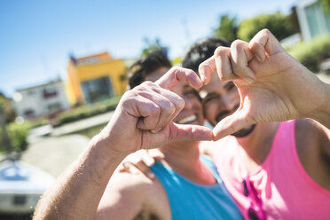 Gay couple in love shaping heart with their fingers - LEF000062