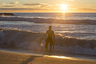 Surfer walking out of the sea at sunrise - SKCF000085