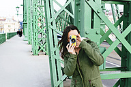 Hungary, Budapest, Young woman on Liberty bridge taking pictures - GEMF000825