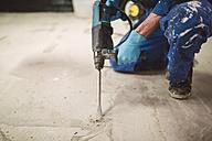 Bricklayer removing irregularities on floor screed with jackhammer - RAEF000991