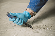 Bricklayer removing irregularities on floor screed with spatula - RAEF000994