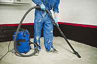 Bricklayer cleaning the floor with an industrial vacuum cleaner - RAEF001000
