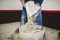Bricklayer pouring cement powder in bucket - RAEF001009