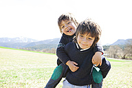 Portrait of little boy carrying his brother piggyback - VABF000420