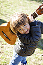 Portrait of smiling little boy with Spanish guitar - VABF000423