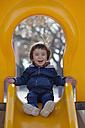 Portrait of laughing little boy sitting on a yellow shute - XCF000074