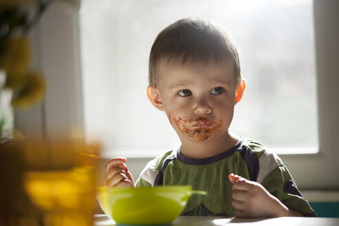 Serious looking little boy eating chocolate - ZEDF000080