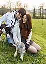 Young couple with their dogs on a meadow - MGOF001706