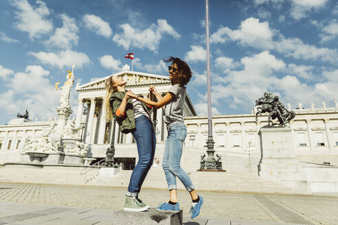 Austria, Vienna, two young women having fun in front of the parliament building - AIF000300