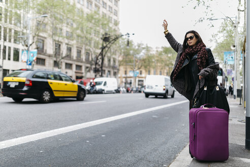 Spain, Barcelona, young woman with suitcase hailing a taxi - JRFF000510