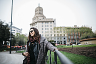Spain, Barcelona, smiling young woman in the city - JRFF000513