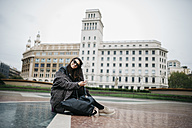 Spain, Barcelona, smiling young woman sitting  on Placa Catalunya - JRFF000516