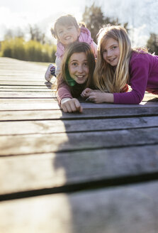 Group picture of three girls on a boardwalk pulling funny faces - MGOF001709
