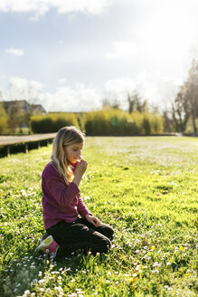 Little girl crouching on a meadow smelling daisy - MGOF001712