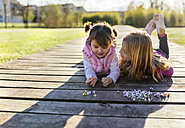 Two little girls lying on a boardwalk looking at each other - MGOF001718