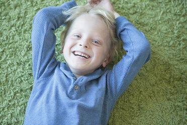 Portrait of happy little blond boy lying on green carpet - RBF004246