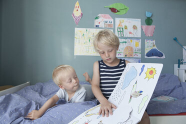 Two little brothers on bed at children's room watching picture book - RBF004252
