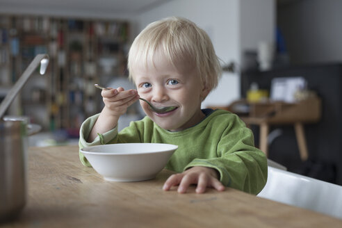 Portrait of smiling little boy eating soup at home - RBF004264