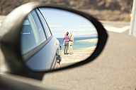 Spain, Fuerteventura, Jandia, reflection of family at the coast in wing mirror of a car - MFRF000591