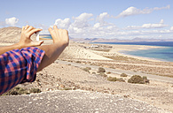 Spain, Fuerteventura, Jandia, man taking picture at the coast - MFRF000594