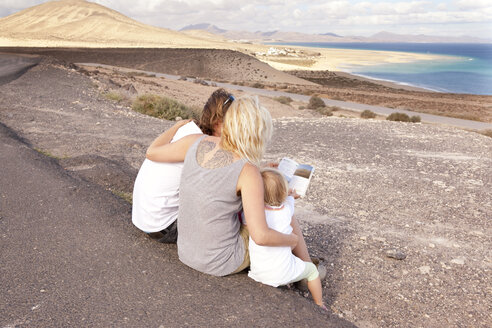 Spain, Fuerteventura, Jandia, family sitting at the coast looking in guidebook - MFRF000597