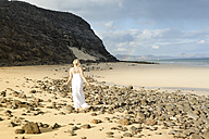 Spain, Fuerteventura, Jandia, woman walking on beach - MFRF000600