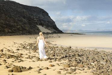 Spain, Fuerteventura, Jandia, woman walking on beach - MFRF000600