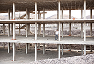 Spain, Fuerteventura, Jandia, architect standing in building shell - MFRF000612