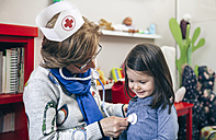 Senior woman with nurse cap checking her granddaughter with toy stethoscope - DAPF000090
