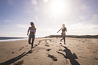 Spain, Tenerife, two female friends running on the beach - SIPF000331
