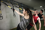 Group of young people training on elastic cord in gym - JASF000622