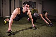 Man and woman doing crossfit exercises in gym - JASF000634