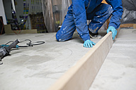 Worker checking the level of the concrete floor - RAEF001029