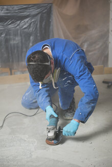 Worker smoothening cement with an angle grinder - RAEF001044