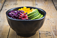 Lunch bowl with black rice, avocado, yellow bell pepper, red cabbage and pomegranate seed on wood - LVF004727