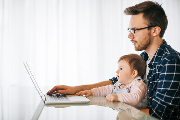 Young man with baby girl on his lap trying to work - BRF001298